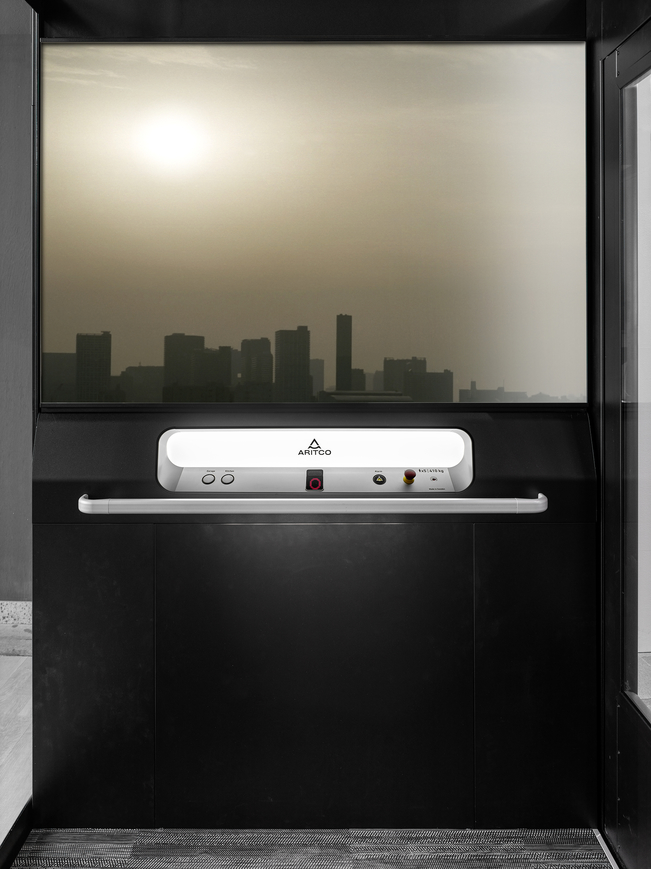 The home lift Aritco Homelift access with a designwall with a skyline