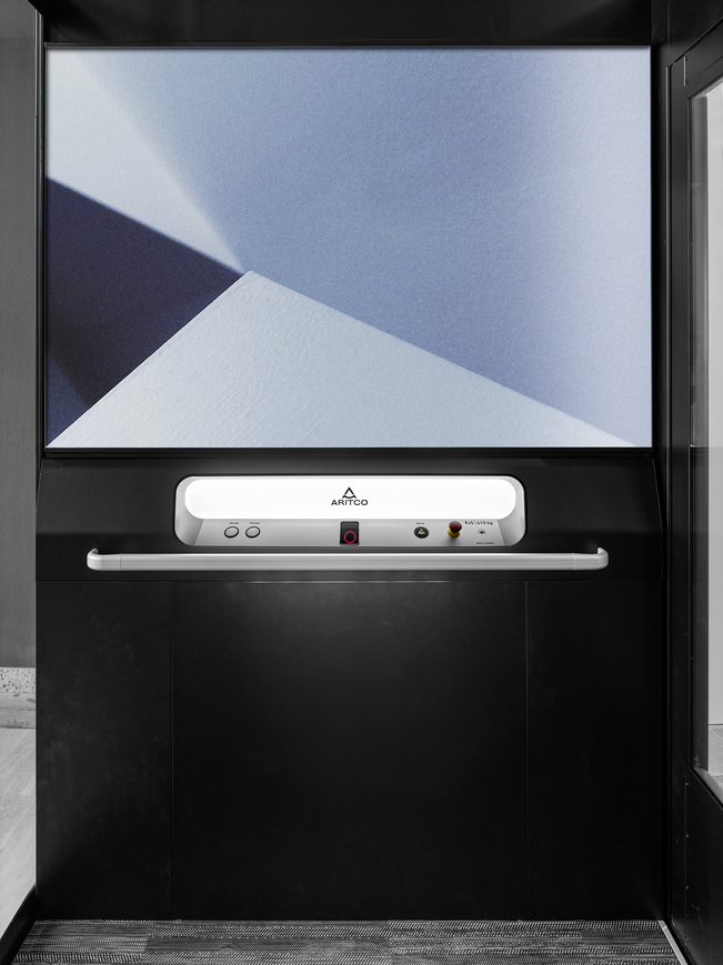The home lift Aritco Homelift access with a designwall in blue colours